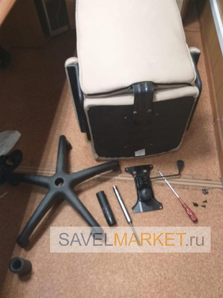 мастер снял поломанный газлифт с офисного кресла